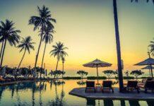 Egipt leżaki palmy i parasolki przy zachodzie słońca