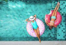 Dwie kobiety w basenie pływające na dmuchanych pączkach