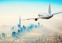 samolot lecący w stronę wieżowców