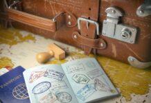 pieczątki w paszporcie leżącym obok walizki