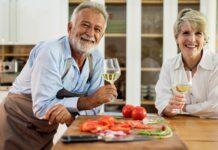mężczyzna i kobieta trzymający kieliszki z białym winem w kuchni na tle białego regału