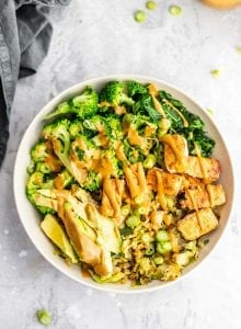 Cabbage, broccoli, tofu, avocado, kale and almond butter sauce in a low-carb vegan dinner bowl.