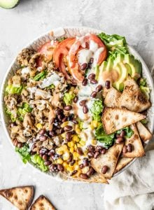 Vegan taco salad with lentils, tomato, corn, avocado and tofu sour cream in a bowl.