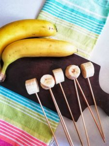 Bananas are shown cut into pieces and skewers are inserted.