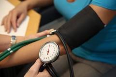 Arzt mit Stehtoskop misst Patient den Blutdruck