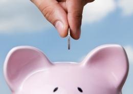 Rosa Sparschwein und Hand, die Geld einwirft