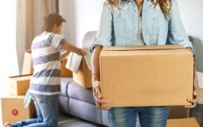 Junges Pärchen zieht in die neue Wohnung und trägt Umzugskartons