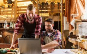 Handwerker zeigt anderem Handwerker blauarbeit.de auf einem Laptop