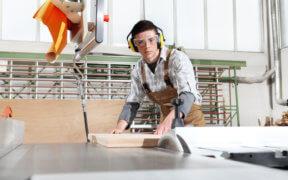 Junger Tischler schneidet ein Brett mit der Kreissäge, er trägt Gehörschutz und Schutzbrille