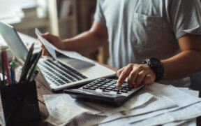 Ein Mann tippt etwas auf einem Taschenrechner, auf dem Tisch liegen viele Rechnungen