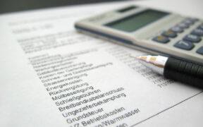 Auf einer Betriebskostenabrechnung liegt ein Stift und ein Taschenrechner