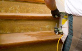 Holz abschleifen, um die Treppe zu sanieren.