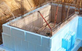 Rohbau eines Kellers, außen kleben hellblaue Dämmplatten