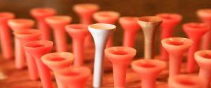 weisser Golf Tee in Menge roter symbolisiert USP