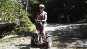 Segway Fahrerin mit Helm bei Bach Durchfahrt