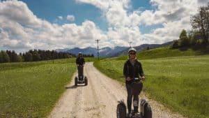 zwei Segway Fahrer auf Weg im Leitzachtal und im Hintergrund die Berge