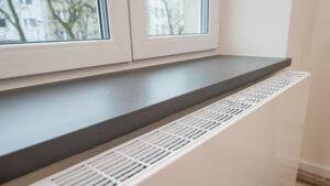 Ein Plattenheizkörper unter einer Fensterbank