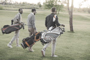 group of the 3 male golfers carrying golf bags