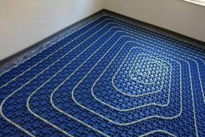 Wasserleitungen liegen gleichmäßig verteilt am Boden eines Raums