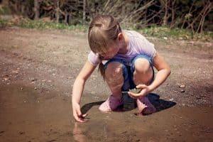 Leben im Moment - Kind spielt in Pfütze