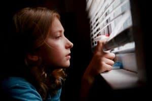 nicht mehr einsam: Mädchen schaut achtsam durch die Jalousie nach draußen