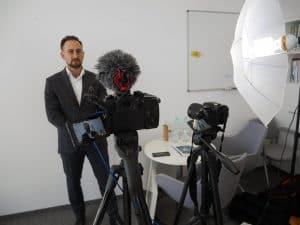 Mężczyzna ubrany w garnitur stojący przed kamerą i opowiadający o nowej aplikacji.