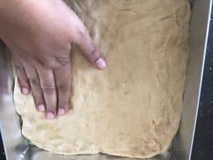 Spreading the focaccia dough to a greased tin