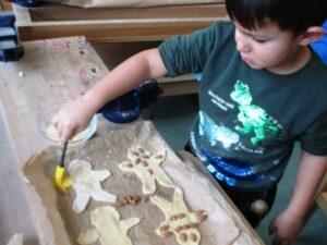 Ein Junge bemalt Plätzchen mit einem Pinsel.