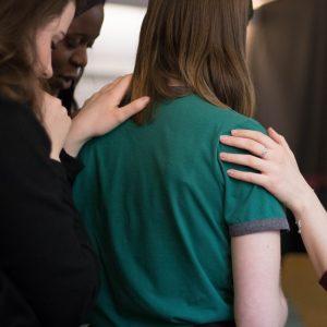Frau erhält Unterstützung durch Menschen, die die Hände auf ihre Schultern legen.