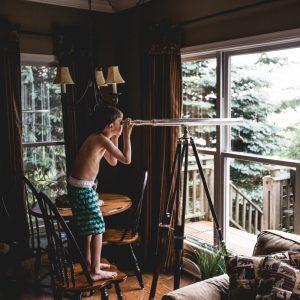Mut: Junge schaut durch ein Fernrohr aus dem Fenster