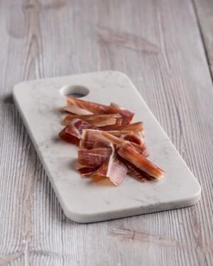 Jamón Ibérico de Cebo loncheado sobre tabla de mármol blanca y fondo madera clara