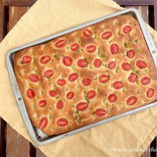 Overhead photo of cherry tomato focaccia on a baking sheet and yellow napkin