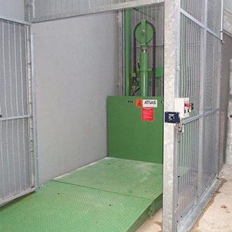 Monte-charge industriel: Vue intérieure de la cage avec porte ouverte et plateau élévateur en position basse.