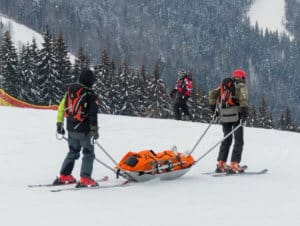 Injured Skier Being Taken For Care - Sports Injuries - Personal Injury Law