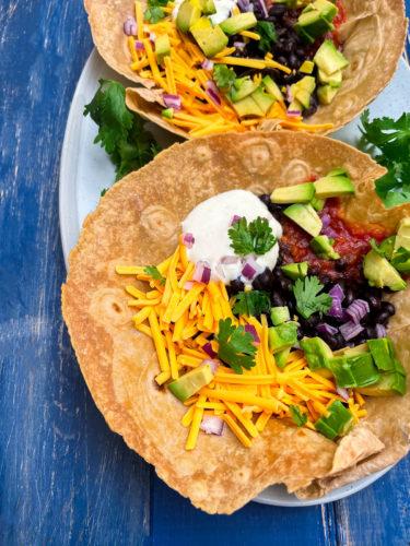 overlay taco salad in taco bowl with tofu crumbles, black beans, soy cream, vegan cheese, salsa, avocado, cilantro, red onion