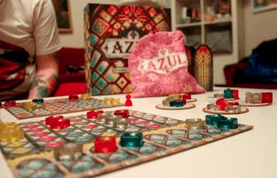 Azul-pelaajan oma lauta, taustalla pelilaatikko ja laattapussi