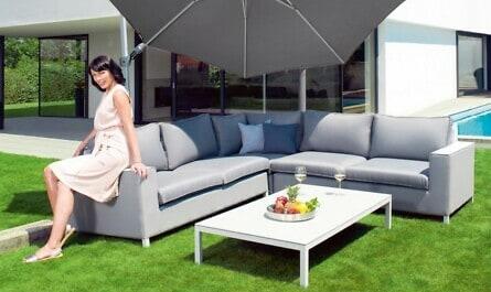 Frau unter Sonnenschirm im Garten
