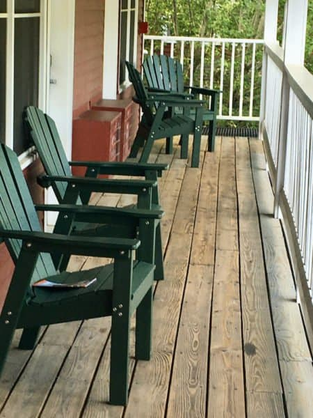 An outdoor porch with adirondack chairs in the green mountain inn annex