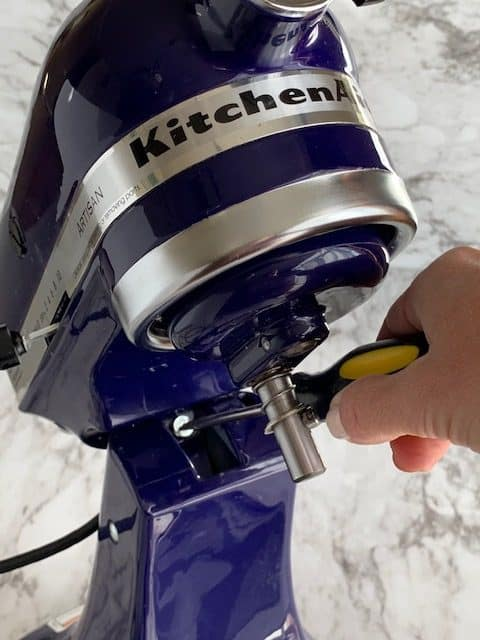 Artisan KitchenAid mixer with adjustment screw exposed and screwdriver