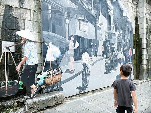 A boy walking past a mural in Hanoi, Vietnam