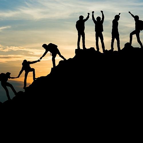 Gruppe von Menschen auf Gipfel. Bergsteiger helfen einander - Teamarbeit.