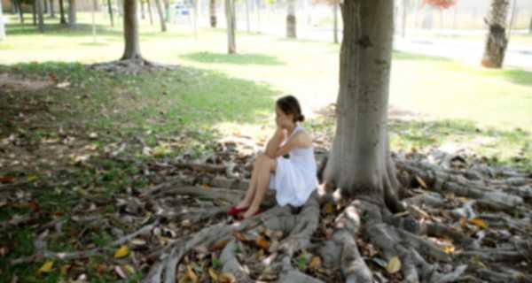 bambina seduta sotto albero pensa