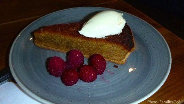 A slice of treacle tart with whipped cream and rasberries in edinburgh.