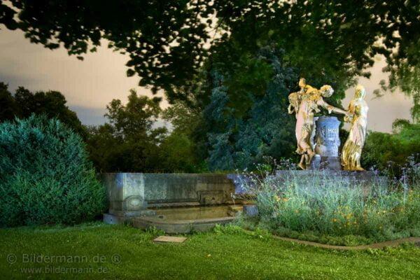 """""""BUNTBILD""""-Nachtaufnahme vom Mozartbrunnen (Dresden). Der Mozartbrunnen ist ein Brunnen im Landschaftsgarten Bürgerwiese im Dresdner Stadtteil Seevorstadt-Ost/Großer Garten. Der Brunnen wurde vom Bildhauer Hermann Hosaeus (1875-1958), Berlin im Auftrag des Mozartvereins Dresden  von 1902 bis 1907 geschaffen. Die 3 weibl. Figuren (Anmut - Heiterkeit - Ernst) sollen die Musik Wolfgang Amadeus Mozarts in Form eines Reigens verkörpern. (Bild unter zur Hilfenahme einer LED-Taschelampe bei Nacht entstanden. Die teilweisen Unschärfen im Bild sind vom leichten Wind während der Langzeitbelichtung.)"""