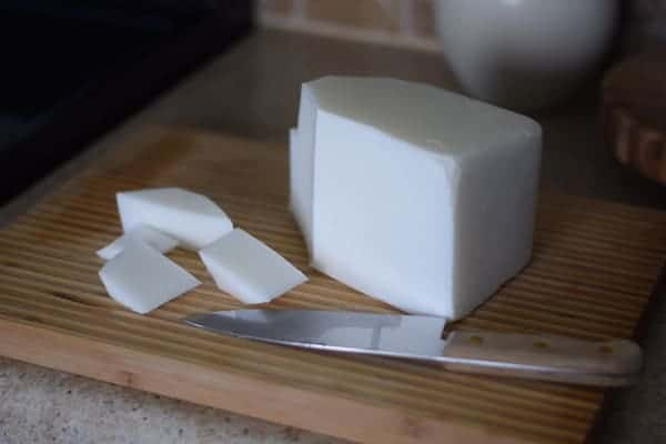 block of goat milk soap base with a large knife on a cutting board