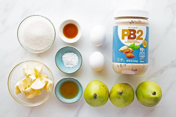 Pear Frangipane tart ingredients laid out: butter, sugar, amaretto, vanilla, baking powder, 2 eggs, PB2 almond powder, 3 pears
