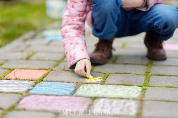 Child drawing with sidewalk chalk