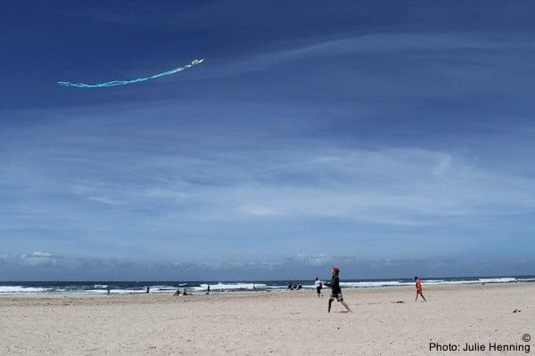 A family flies a kite on rockaway beach in oregon. The beach is empty, the sky is blue.
