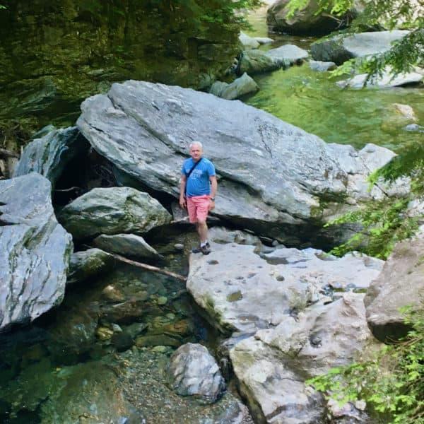 A man poses among the large granite rocks at the bottom of bingham falls.