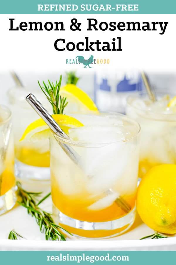 Tray with four glasses of iced lemon & rosemary cocktail with lemon wedges, fresh rosemary and stainless steel straws long pin.